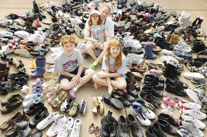 Rachel Quade sits in her Columbia driveway on Tuesday, Aug. 16 with her children, from left, Stephen, 11, Sarah, 7, and Grace, 10, surrounded by the more than 200 pairs of shoes collected over the weekend.