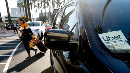 A passenger exits an Uber car at Union Station in Los Angeles.