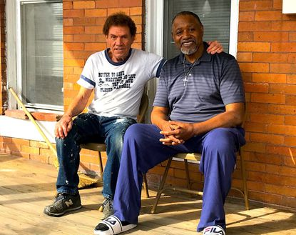 Kurt Wenzing and Calvin Ash, who have become friends, on the front porch of the Ash home in Wilson Park in Baltimore.