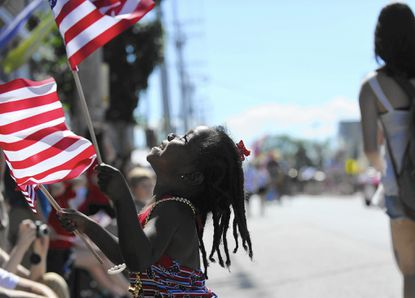 Alia Jeter, 4, of Fulton waves her flags and laughs during the 68th annual Catonsville 4th of July parade. (Rachel Woolf, Baltimore Sun /July 4, 2014)