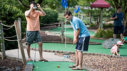 Drew Tyler sets up to tee off on the seventh hole at the miniature golf course inside Columbia SportsPark.