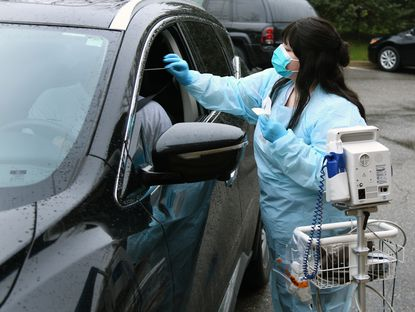 Medical technician Casey Dews removes a test swab from a person who is not feeling well to be tested for flu, RSV and Strep. Chesapeake ERgent Care, in Gambrills, started drive-thru coronavirus testing Monday for a select people that meet CDC criteria and test negative for other viruses.