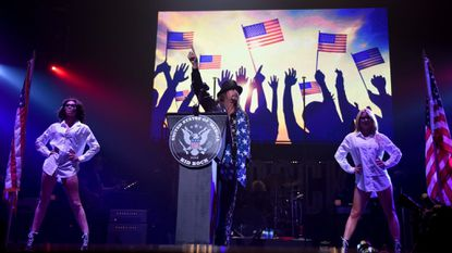 """Kid Rock gives a speech behind a """"United States of 'Merica"""" podium during his performance at Little Caesars Arena in Detroit on Sept. 12. The rock musician will perform in Baltimore in March."""