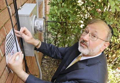 Jonathan Libber, 59, president of the Maryland Smart Meter Awareness organization, tapes a warning sign next to the analog meter at his home in the Greenspring neighborhood. The sign warns against trespassing and says that the homeowner does not give permission to have a Smart Meter installed.