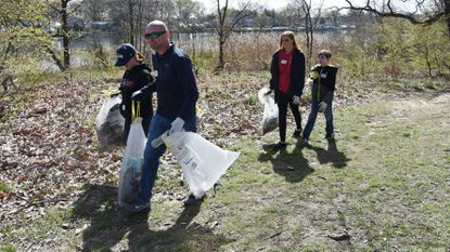 Dundalk, Md -- Lisa Slattery and her fiance, Damien Surguy, and his children, Autumn Surguy, 18, and Damien Surguy, 10, carry bags of litter they have collected. They are volunteering through CityFam at Saturday's clean up of Bear Creek Park and its shoreline.