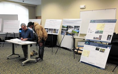 Jonathon Kusa, left, a project manager with Inter-Fluve, answers questions from Bobby Barker, of Ellicott City, about a plan to remove the Bloede Dam from the Patapsco River. The plans were presented at the Arbutus Llibrary on Thursday. Environmental officials say the dam is blocking migratory fish and also poses a public safety risk.