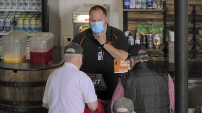 Fans order food from a masked employee during the Orioles' Opening Day at Oriole Park at Camden Yards on Thursday, April 8, 2021. (Karl Merton Ferron/Baltimore Sun)