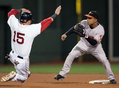 Orioles shortstop Cesar Izturis (right) waits for the throw as Boston Red Sox second baseman Dustin Pedroia attempts a stolen base in the sixth inning at Fenway Park. Pedroia was caught stealing on the play.