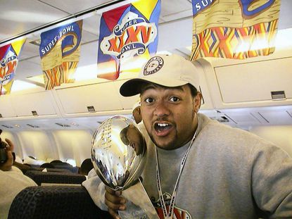Former Ravens linebacker Brad Jackson shows off the Super Bowl XXXV Trophy in 2001 on the flight back from Tampa Bay after the Ravens beat the Giants 34-7.