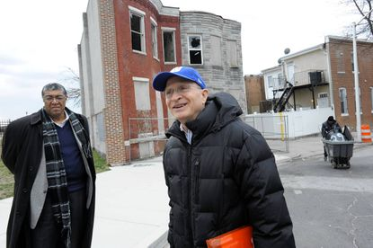 Michael Barland, executive director urban development hor Housing Services Alliance, (left) and Kevin Bell, senior vice president of development for The Woda Group, LLC, stand outside two of several row homes that will be renovated and sold along the 1600 block of Clifton Ave.
