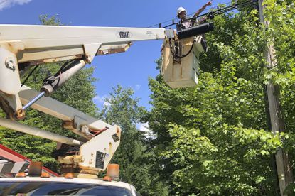 A technician works on a line used to provide broadband internet service in a rural area on Wednesday, July 29, 2020, in Stowe, Vt. Vermont officials are working to expand internet service using federal pandemic relief funds. But they are scrambling because the projects, which can frequently take years to plan and build, must be done by the end of the year. (AP Photo/Wilson Ring)