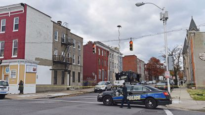 Baltimore Police on Sunday work the area in West Baltimore where Detective Sean Suiter was fatally shot Wednesday. Police are still searching for a suspect in the killing.
