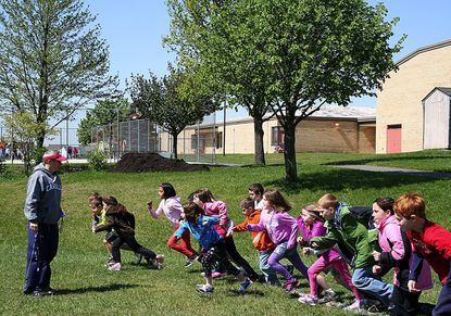 Second graders at Hampstead Elementary School race past Ronnie Rebhan, physical education teacher, as they practice the 400-meter run during gym class April 24.