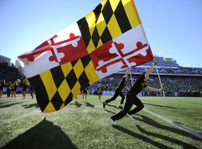 Eddie Yacynych, front, and Robert Bailey run with Maryland flags across the field during pregame festivities before the Military Bowl at Navy-Marine Corps Memorial Stadium last season.