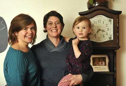 Katie Dongarra, 33, left, and Sharon Dongarra, 37, right, with their two year old daughter Lucy, plan to be legally wed after midnight on New Year's Day at their home in front of this clock, with friends and family gathered around them. They have been together for 17 years, and had a symbolic marriage ceremony in 2006.