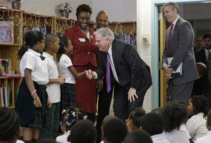 Maryland Gov. Larry Hogan, center, greets students before taking part in a reading exercise at Empowerment Academy charter school, Feb. 18, 2015, in Baltimore.