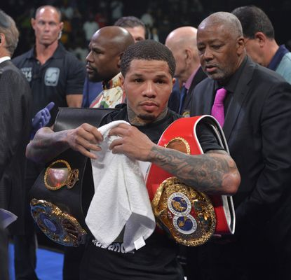 """Gervonta """"Tank"""" Davis holds his championship belts after defending his super featherweight title at Royal Farms Arena."""
