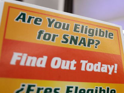 As many as 15,000 people in Baltimore could see their food stamp benefits slashed under a new Trump administration rule that tightens eligibility requirements. In this Jan. 23, 2019, photo, a booth at Newark Liberty International Airport in New Jersey offered information about food stamps at a food drive.