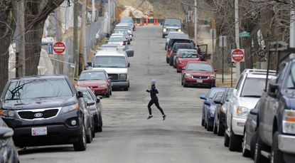 Cars parked along 38th St. as a runner passes through on Elm Ave.
