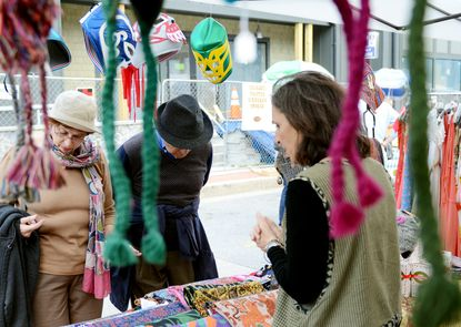 From left, Merle Ann and Stan Siegelman look through items at Cindy Marcoline's booth at the Mount Washington Village Fall Block Party.
