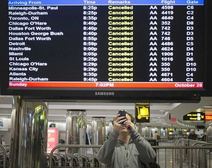 An air traveler takes pictures of a flight monitor showing cancelled flights at New York's LaGuardia Airport
