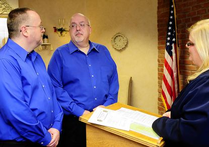 Casey Anno, left, and David Wilhelm, of Havre de Grace, exchange wedding vows at the Clerk of the Court's Marriage Room Wednesday afternoon in Bel Air. They are the first gay couple to be married in the civil marriage room.