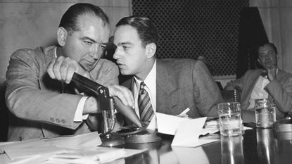 Sen. Joseph McCarthy covers the microphones with his hands while having a whispered discussion with his chief counsel Roy Cohn during a committee hearing on April 26, 1954, in Washington. The entire event of the Senate subcommittee hearings on the Army-McCarthy charges was broadcast live on network TV and radio. McCarthy is the focus of PBS documentary airing Jan. 6.