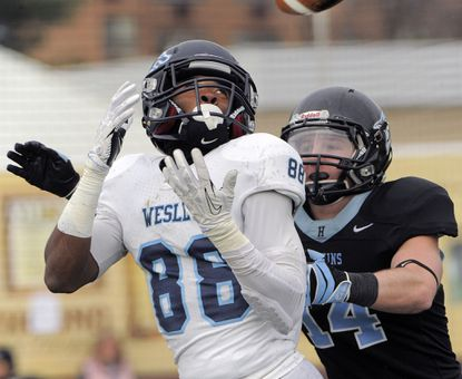 Johns Hopkins defensive back Ryan Rice (14) follows Wesley wide receiver Steve Koudossou (88) who looks a pass into his hands for a touchdown during the opening round of the NCAA Div. III tournamen.