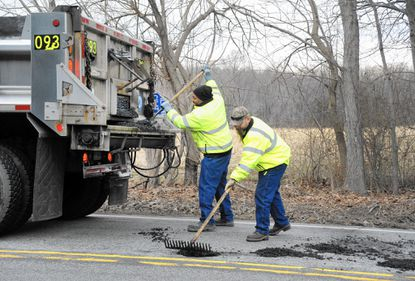 County workers Robin Roberts II, left, and Jason Lawson the fill some of the many potholes along Prospect Mill Road Wednesday morning.