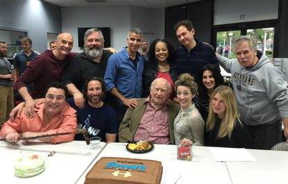 """Veteran TV and film actor Ed Asner (seated middle) at table-read with the cast and crew for a sitcom pilot, """"Bennie's Gym,"""" filming in Columbia."""