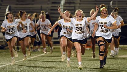 South Carroll's Courtney Vasquenza leads the team's charge across the field to celebrate with fans after their win over Hereford during the Class 2A girls lacrosse state championship game at Paint Branch High School last year. The recent decision to cancel high school spring sports means there will be no repeat performance in 2020.
