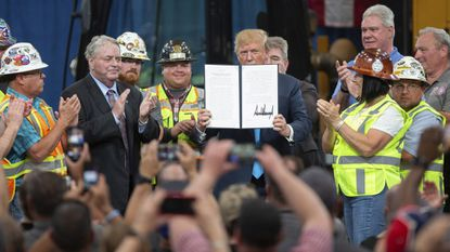 President Donald Trump holds up an executive order on energy and infrastructure after signing it at the International Union of Operating Engineers International Training and Education Center on Wednesday.