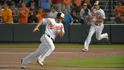 Orioles' Chris Davis (19) heads for third base on a double from batter Matt Wieters (32) at Camden Yards on Aug. 20, 2015.