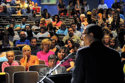 Concerned citizens listen as principal George Roberts speaks at a community meeting at Perry Hall High School.