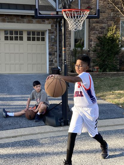 Khasan Al-Mateen dribbles the ball while his friend Cooper Chasm takes a break during a game of basketball.