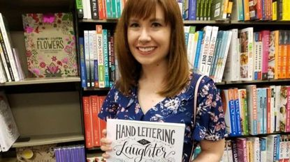 """Author Amy Latta finds her new title """"Hand Lettering for Laughter: Gorgeous Art With a Hilarious Twist"""" in the bookstore."""