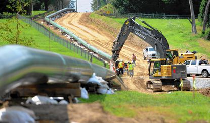 Crews work Tuesday on a section of the new four-mile gas pipeline along Route 136 in Churchville.