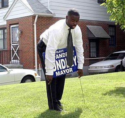 Andrey Bundley, a contender in the city's Democratic primary, plants a campaign sign on a backer's lawn on Cedonia Avenue.