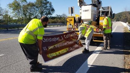 A crew mounts a sign on a Dulaney Valley Road bridge over Loch Raven in October dedicated to the memory of Timonium native Army Cpl. Christopher Coffland, who was killed in action in Afghanistan in November 2009.