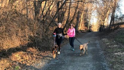 Rhonda Utz, left, with her dog Kobie, and Margie Gallagher, with Maverick, run the Ma & Pa Trail from Williams Street to Tollgate Road late Saturday afternoon.