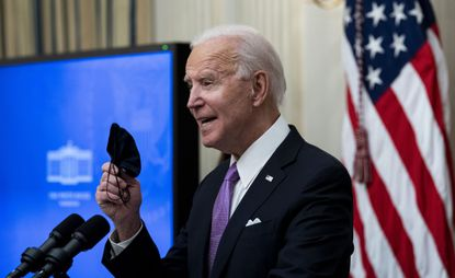 """President Joe Biden displays his face mask as he talks about his administration's COVID-19 response plan during an event at the White House in Washington on Thursday, Jan. 21, 2021. President Biden, pledging a """"full-scale wartime effort"""" to combat the coronavirus pandemic, signed a string of executive orders and presidential directives on Thursday aimed at combating the worst public health crisis in a century, including new requirements for masks on interstate planes, trains and buses and for international travelers to quarantine after arriving in the United States."""
