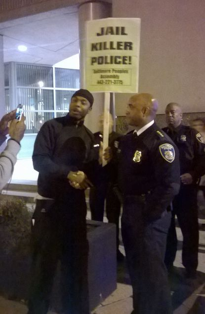 Commissioner Anthony Batts shakes hands with a man during last night's Ferguson protests.