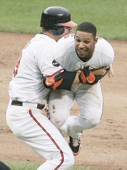Robert Andino, right, gets a bearhug from Orioles teammate Chris Davis after driving in the winning run against the Yankees in the bottom of the 10th inning.