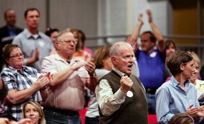 Residents against the Woodmont Academy development stand and cheer during an April 8, 2013, hearing held by the Howard County Planning Board at Glenelg High School.