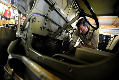 """Eric Hanson works on a 1945 Willys MB at his home in Westminster Saturday. Hanson restored a jeep for an episode of the National Geographic Channel program """"Family Guns"""" which airs Sept. 26."""