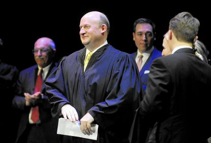 Richard Titus stands on stage after donning his robe with the help of his wife and children during his investiture as an associate judge for the Circuit Court for Carroll County at Carroll Community College in Westminster Friday, March 11.