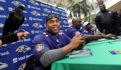 Jamal Lewis poses with Ravens mascot Conquer from the Maryland Zoo, at M & T Bank's Ravens Flock Party at White Marsh Mall.