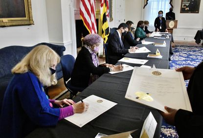 Corynne B. Courpas, treasurer of the Carroll County Democratic Central Committee, front, Thelma T. Daley, second from left, and other electors sign the Certificate of Vote during the 59th meeting of the Maryland Electoral College at the State House.