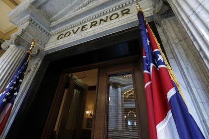 The Mississippi state flag is shown across from the American flag, outside the Governor's Office at the Capitol in Jackson, Miss., Monday, June 29, 2020, the day after both chambers of the state Legislature passed a bill to take down and replace the current flag, which contains the Confederate battle emblem.