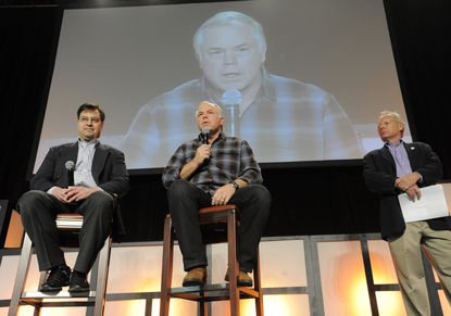 Dan Duquette, left, listens as Buck Showalter addresses the FanFest audience in 2013.